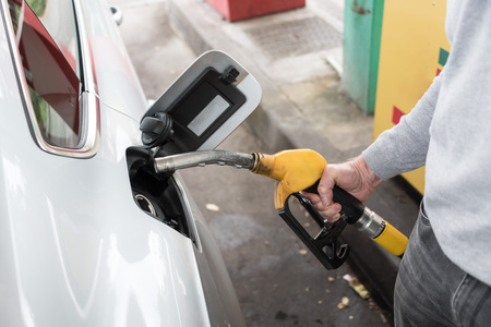 fueling: Man holding a yellow fuel pump nozzle