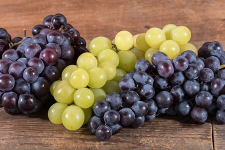bunches: Bunches of white and black grapes, on wooden background