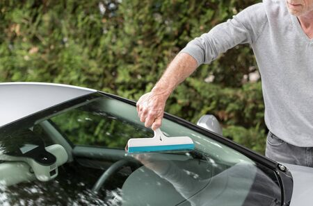 squeegee: Man cleaning a windshield with a squeegee