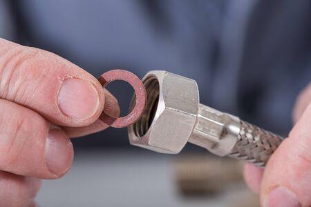 gasket: Plumber putting a gasket on a plumbing fitting, closeup