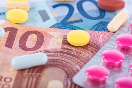 health care costs: Concept of health care costs with pills and banknotes