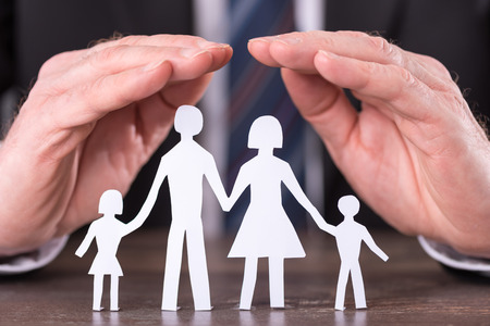 Concept of family insurance with hands protecting a family Stockfoto