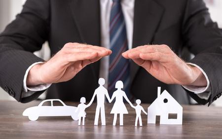 Concetto di assicurazione con le mani su una casa, una macchina e una famiglia Archivio Fotografico - 51688169