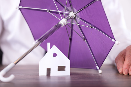 protection concept: Concept of home insurance with umbrella protecting a house