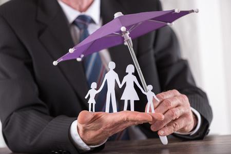 Il concetto di famiglia di assicurazione con l'ombrello proteggere una famiglia Archivio Fotografico - 51688171