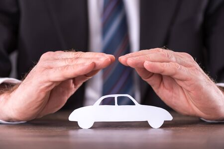 Concept of car insurance with hands over a car