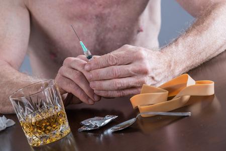 drug addict: Drug addict preparing a dose of heroin Stock Photo