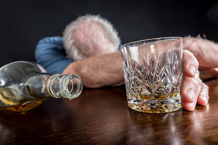 slumped: Drunk man slumped on table after alcohol abuse