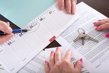 Real estate agent showing the effective date of lease on calendar (random english dummy text used) Imagens