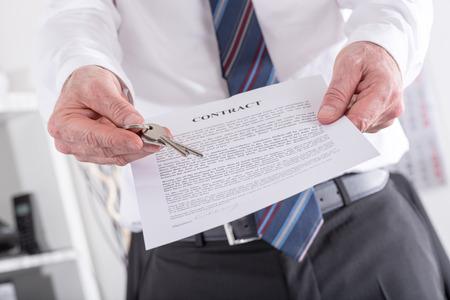 Immobilienmakler geben Hausschlüssel mit Vertrag (random Englisch Blindtext verwendet)