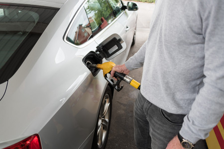 nozzle: Man holding yellow fuel pump nozzle and refilling car Stock Photo