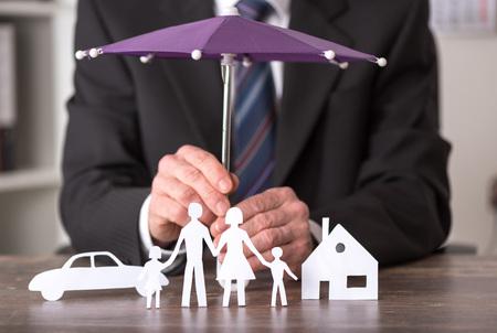 Concetto di assicurazione con l'ombrello sopra una casa, una macchina e una famiglia