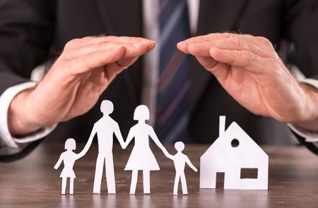 Het concept van de verzekering met de handen over een huis en een gezin Stockfoto