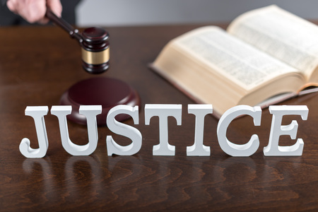 verdicts: Justice concept with hand holding a judge gavel Stock Photo