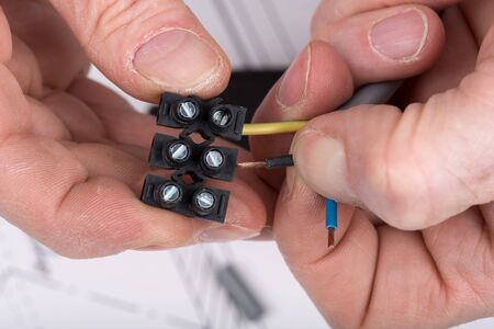 connector: Hand putting a wire in a connector Stock Photo