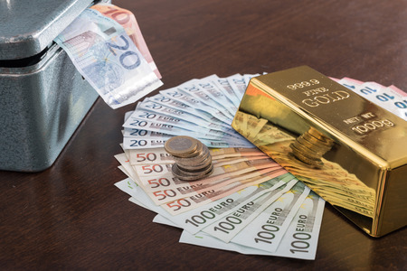 Banknotes, ingot and cash box on a table