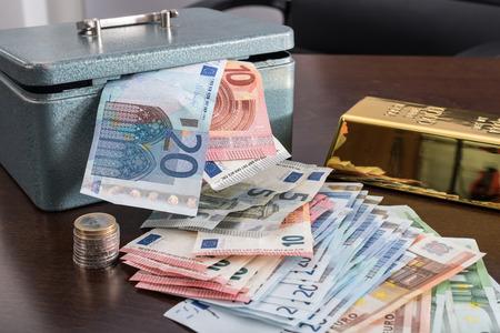 ingot: Banknotes, ingot and cash box on a table