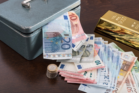 cash box: Banknotes, ingot and cash box on a table
