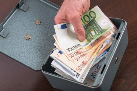 withdrawing: Hand withdrawing money from a metal box