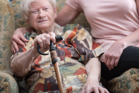 needy: Old woman supported by young woman Stock Photo