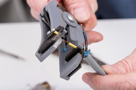 stripper: Action to strip a wire with a wire stripper, closeup Stock Photo
