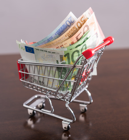 finance concept: Small trolley full of euro banknotes