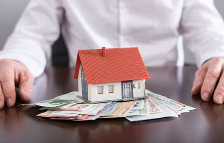 Estate agent and house on banknotes Stock Photo