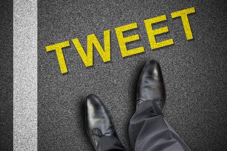 tweet: Feet in front of word tweet printed on the road Stock Photo