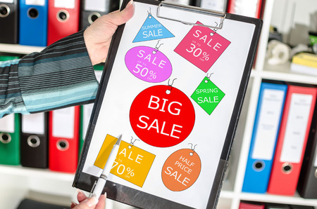 Woman holding a clipboard with sale concept