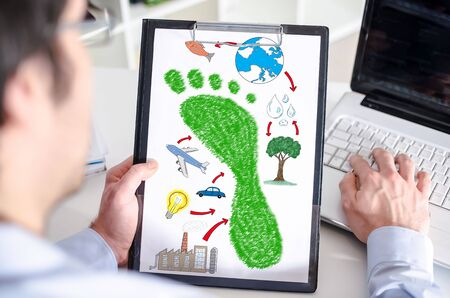 carbon footprint: Man holding a clipboard with carbon footprint concept