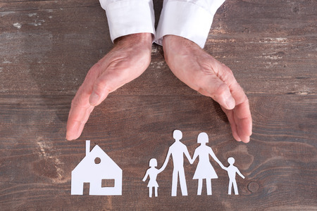 insurer: Family and house covered by hands - insurance concept
