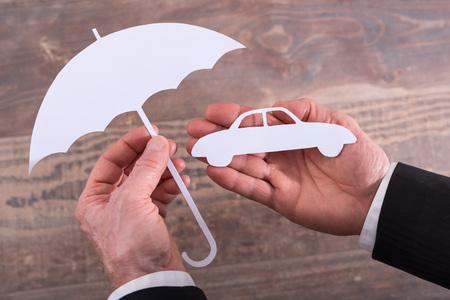 insurer: Hands holding a car and an umbrella - insurance concept