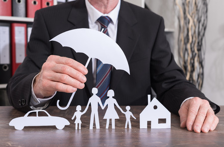 House, car and family protected with an umbrella by an insurer - insurance concept Foto de archivo