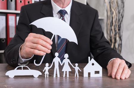 Maison, voiture et famille protégés avec un parapluie par un assureur - le concept d'assurance Banque d'images - 61150731