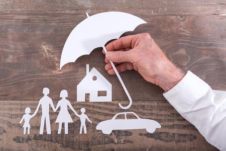 convivencia familiar: Casa, coche y familiares protegidos con un paraguas - concepto de seguro Foto de archivo
