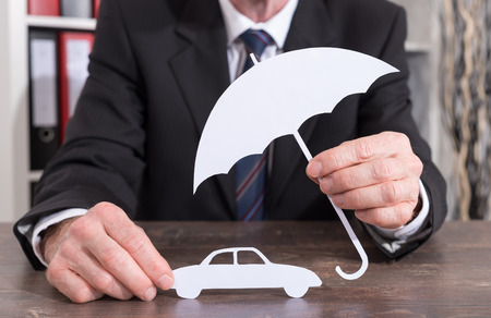 insurer: Car protected with an umbrella by an insurer - insurance concept Stock Photo