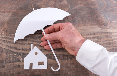 insurer: Hand holding an umbrella to protect a house - insurance concept