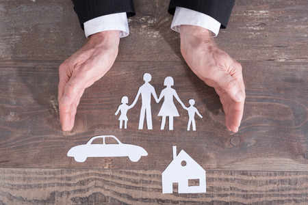 insurer: Family, house and car covered by hands - insurance concept