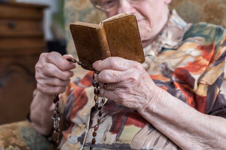 prayer book: Old woman holding a prayer book and a rosary Stock Photo
