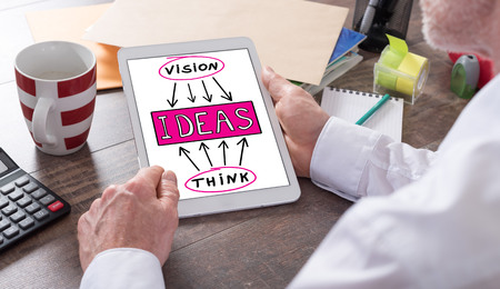 shown: Ideas concept shown on a tablet held by a man Stock Photo