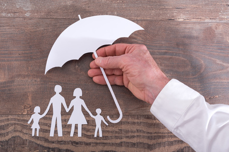 protect: Hand holding an umbrella to protect family - insurance concept