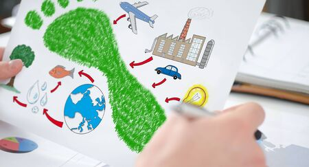 Hands holding a paper showing a carbon footprint concept Stock Photo
