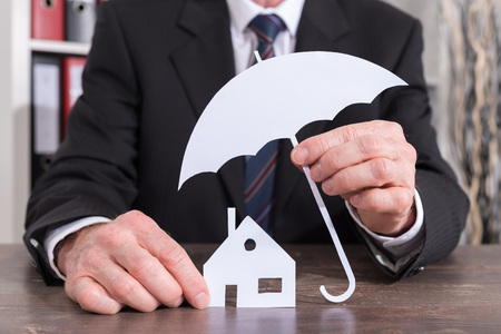 insurer: House protected with an umbrella by an insurer - insurance concept
