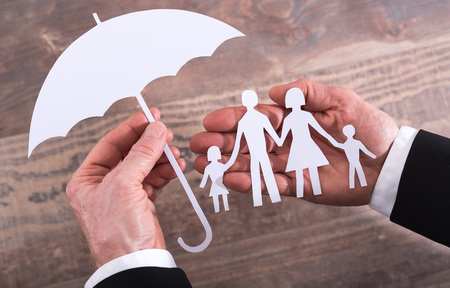 insurer: Hands holding a family and an umbrella - insurance concept