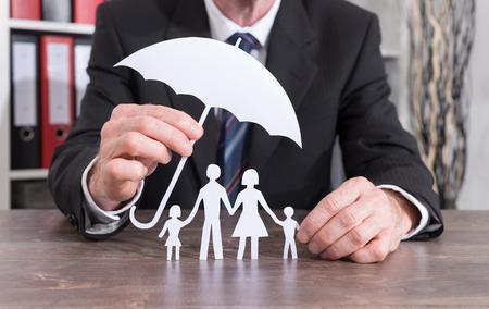 Famiglia protetta con un ombrello da un assicuratore - concetto di assicurazione Archivio Fotografico - 61684211