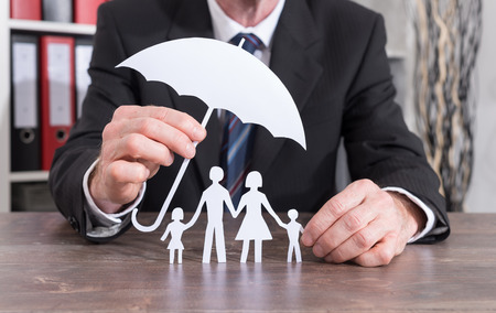 insurer: Family protected with an umbrella by an insurer - insurance concept