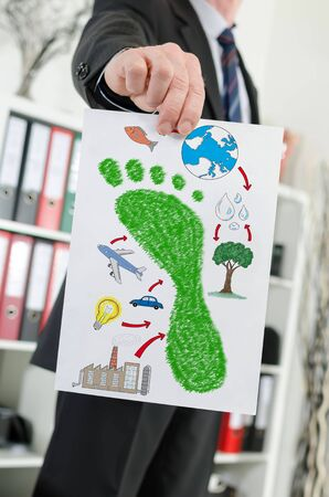 Paper showing carbon footprint concept held by a businessman