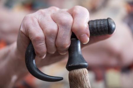 Mano de una persona mayor que sostiene un bastón, primer plano