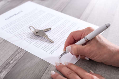 key signature: Female customer signing a real estate contract