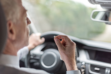 drowsiness: Man taking drugs while driving his car Stock Photo